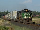 a westbound stack train is led by bnsf 7017. poster