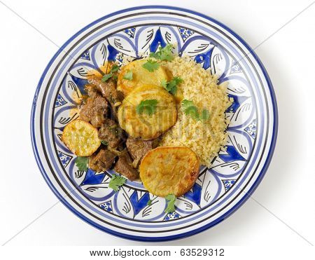 Beef and sweet potato tagine served with couscous and a coriander garnish on a handmade north-African plate, a traditional Moroccan dish from Fez