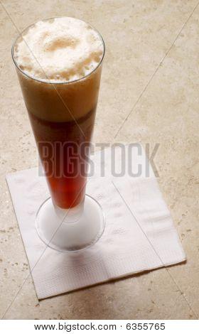 glass of dark beer on stone bar