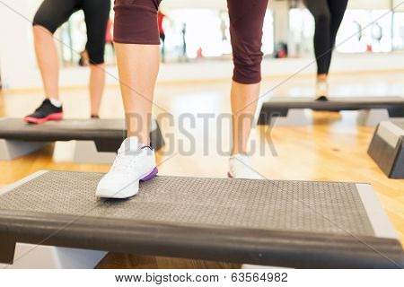 fitness, sport, training, gym and lifestyle concept - close up of women legs steping on step platform in gym