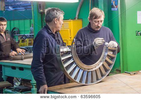 Mechanics assembles turbine for aviation engine