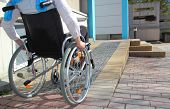 Woman in a wheelchair using a ramp poster