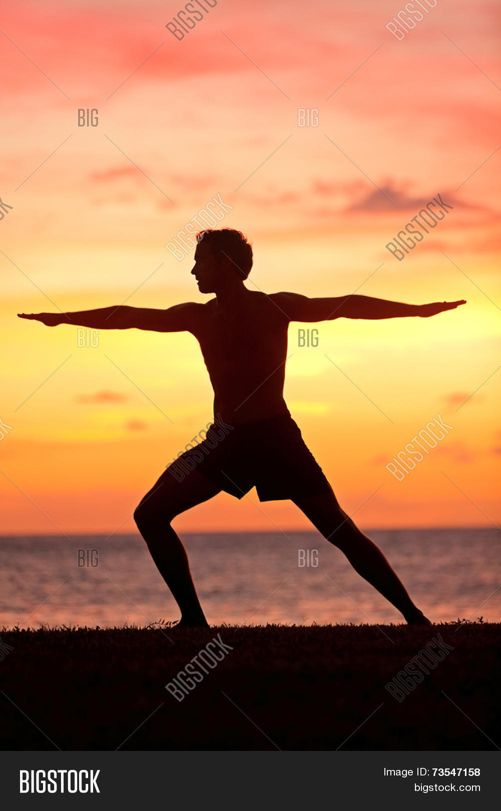 Yoga Man Training And Meditating In Warrior Pose Outside By Beach At Sunrise Or Sunset