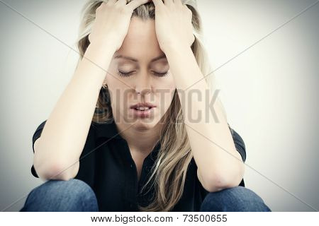 Stressed woman sitting on ground