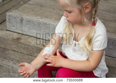 Young girl applying dermatology cream on skin poster
