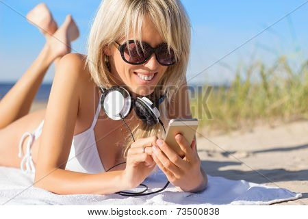 Young woman using mobile phone on the beach