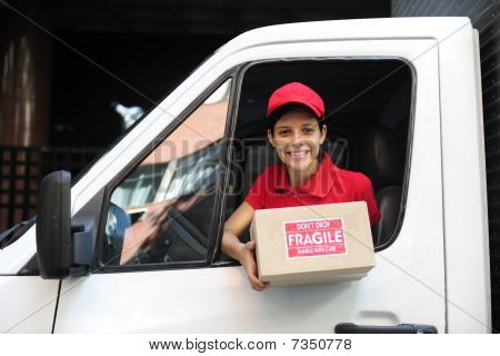 Delivery Courier In Truck Handing Over Package