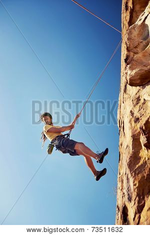A man with dreadlocks in climbing gear rapelling down a mountain against a blue sky with rope