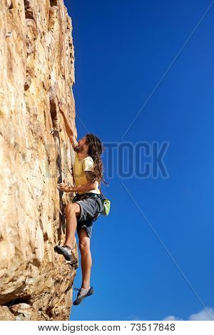 A rockclimbing man reaching for a grip on a steep mountain in the outdoors