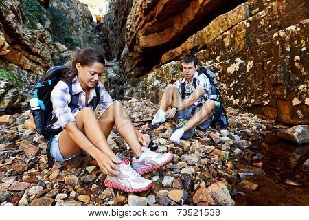 An active couple sitting down and taking a breather from their hike