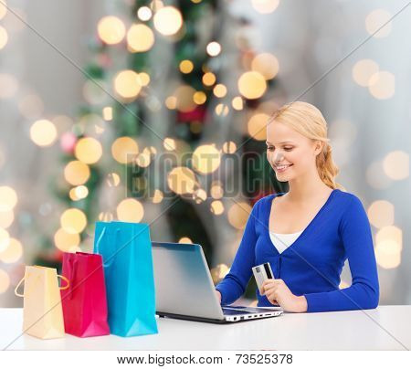 christmas, holidays, technology and shopping concept - smiling woman with shopping bags, credit card and laptop computer over christmas tree background