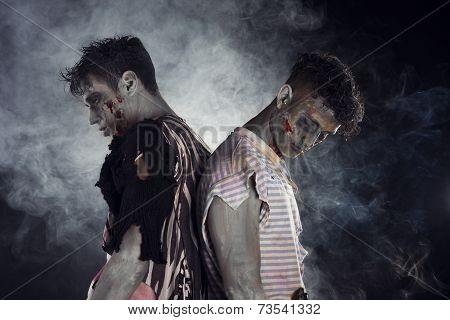 Two Male Zombies Back To Back On Black Smoky Background