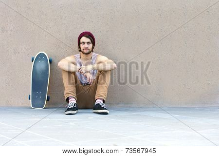 Handsome skateboarder hanging around, sitting against a granite wall, with his skateboard next to him.