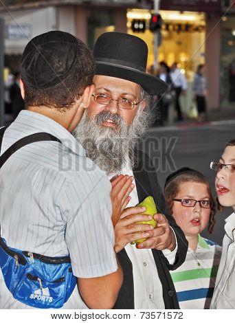 BENE - BERAK, ISRAEL - SEPTEMBER 17, 2013:  The elderly man with gray-haired beard chooses a citrus.  Big market on the eve of Sukkot