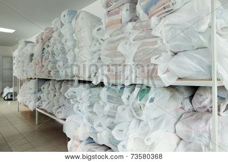 Racks with clean linen in laundry room