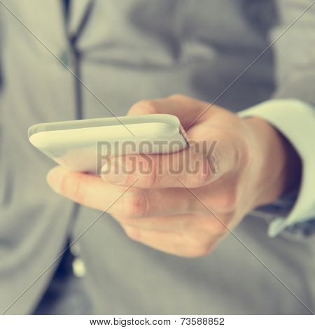 Close-up businessman hand using smart phone in vintage tone.