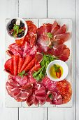 antipasti Platter of Cured Meat,   jamon, sausage, salame  on textured white wooden table poster