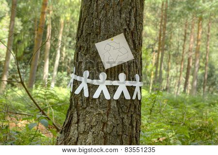 Recycle sign with paper men on a tree