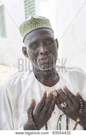 THIAROYE, SENEGAL, AFRICA - JULY 18, 2014 - Unidentified Muslim man praying in front of the Grand Mo