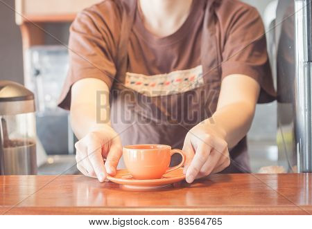 Barista Offering Mini Orange Cup Of Coffee