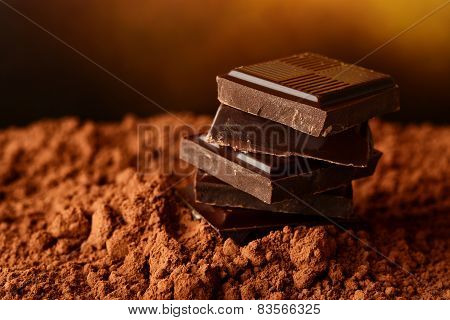 Heap of blocks of chocolate on cocoa powder on dark brown background poster