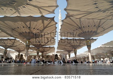 People Sitting In The Courtyard And Rear Visible Minarets Of The Mosque Of The Prophet In Medina Sau