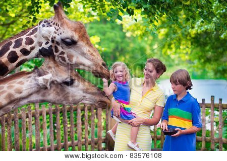 Family Feeding Giraffe In A Zoo
