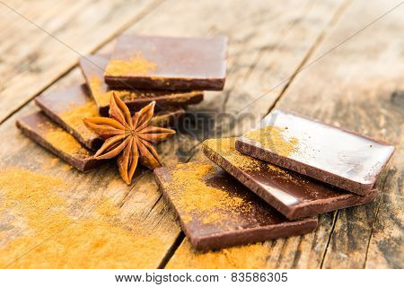 Chocolate on Wood Table Surrounded By Spices.