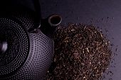 Black Teapot with Healthy Tea Leaves Isolated on Black poster