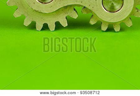 Metal shiny cogwheel element shot on green paper background as closeup image