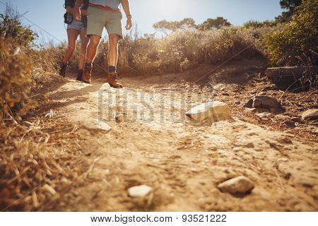 Two People Hiking Along A Dirt Trail