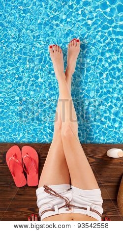 Slim woman legs above swimming pool surface