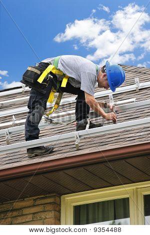 Am Dach, die Installation von Rails für Sonnenkollektoren arbeitender Mann