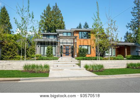 Modern house with wood trim exterior and beautiful landscaping. Home exterior design. poster