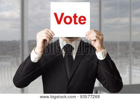 Businessman Hiding Face Behind Sign Vote