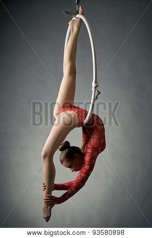 Graceful acrobat performs gymnastic trick on hoop