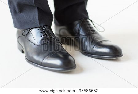 people, business, fashion and footwear concept - close up of man legs in elegant shoes with laces or lace boots