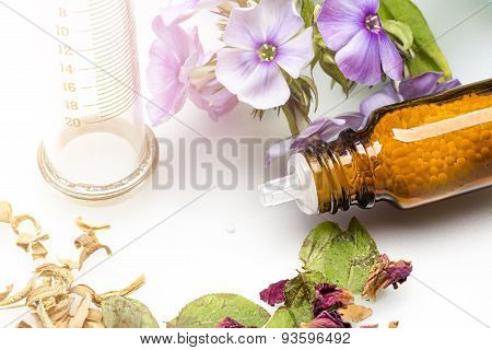 Bottle With Homeopathy Globules, Syringe And Flowers