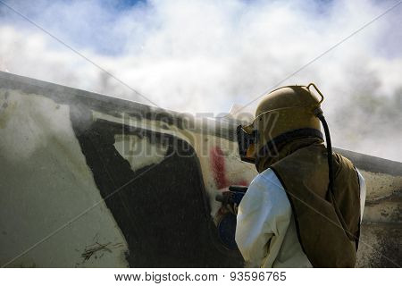 Worker is remove paint by air pressure sand blasting