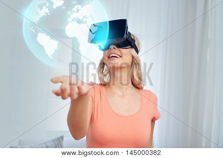 technology, augmented reality, entertainment and people concept - happy young woman with headset or 3d glasses looking at virtual projection of earth globe