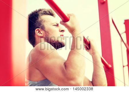 fitness, sport, exercising, training and lifestyle concept - young man doing pull ups on horizontal bar outdoors