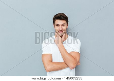 Handsome young smiling pensive man standing and looking up isolated on the gray background
