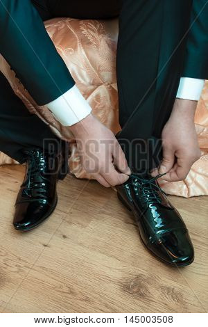 Man Tying Black Patent Leather Shoes