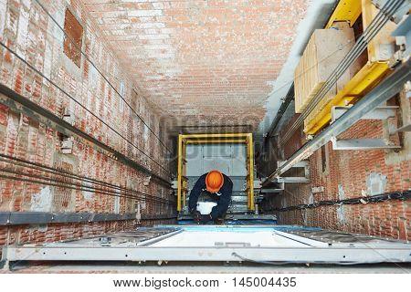 machinists adjusting lift in elevator hoist way