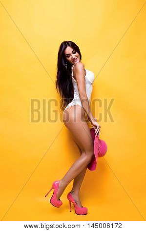 Side view of sexy young model with long hair posing on pink heels with sundown in hands.Yellow background.Isolate.