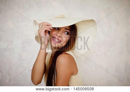Portrait of beautiful lovely brunette woman in white sundown holding it's brim on white background