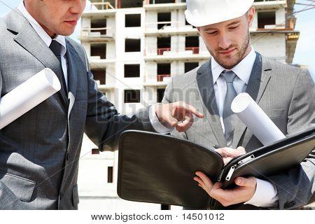 Portret van twee bouwers permanent op de bouwplaats en bespreking van nieuwe project gehouden door een van hen