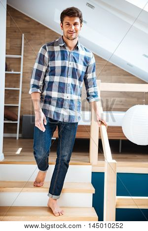Attractive young man in plaid shirt and jeans walking barefoot on stairs at home