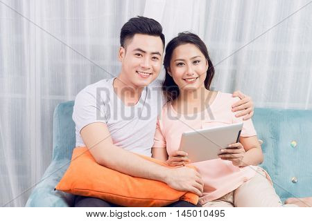 Couple at home relaxing on sofa with digital tablet