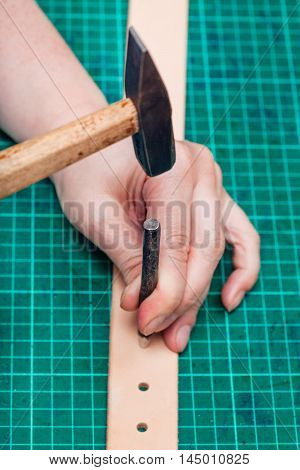 punching holes in leather belt with steel hole punch and hammer on self-healing mat poster